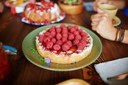 Tasty cake decorated with fresh raspberries on plate Stock Photos