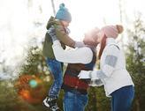Ecstatic family enjoying sunny winter day Stock Photos