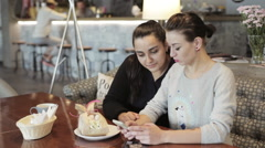 Two young women are talking and using smartphone to show something funny. Stock Footage