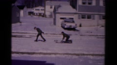 1961: friend pulling boy on sled across suburban winter snowscape HAGERSTOWN Stock Footage