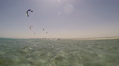 A young man and woman holding hands while kite surfing. Stock Footage