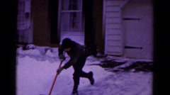 1961: boy playfully shovels snow from driveway during winter HAGERSTOWN Stock Footage