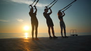 Silhouettes of sportive people training with trx at sea sunrise. Slow motion. Stock Footage