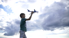 Boy playing with plane on a background of clouds, boy dreams of becoming a pilot Stock Footage