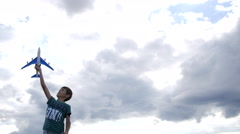 Boy dreams of becoming a pilot, boy playing with plane on a background of clouds Stock Footage