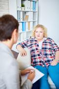 Fat woman talking to counselor during her visit Stock Photos