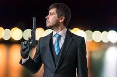 Agent or spy holds gun with silencer in hand at night. Stock Photos