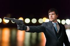 Agent or hitman is aiming with pistol with silencer at night. Stock Photos