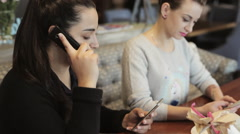 Two womans sitting in cafe and one of them talking on phone. Stock Footage