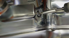 Using a machine to unscrew a big screw in a dishwasher Stock Footage