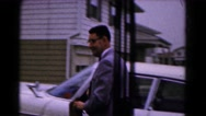 1961: man carrying purse follows lady into house from the car parked nearby Stock Footage
