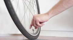 Close-up of young man pumping up bike tire and giving the thumps up sign. Stock Footage