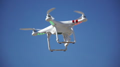 A flying remote-controlled camera drone being operated at the beach. Stock Footage