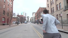 A young man freerunner doing parkour and running in city. Stock Footage