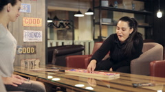 Two yong brunette womans play a board game in cafe. Stock Footage