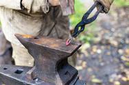Blacksmith forges a buckle on anvil Stock Photos