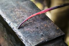 Red hot glowing steel rod on anvil close up Stock Photos