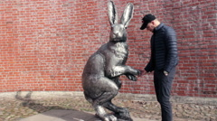 Man Trying to Break Sculpture of Giant Hare Stock Footage