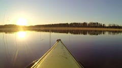 Kayak bow turning towards settin sun at a lake Stock Footage