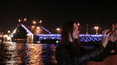 Woman taking selfie. A movable Palace Bridge St. Petersburg at the background Stock Footage