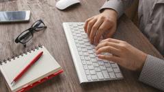 Man arms typing on keyboard at natural hardwood desk Stock Footage