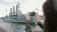 Girl taking photos of Cruiser Aurora St. Petersburg Stock Footage