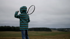 Tennis player boy in the field, boy goes on a field with a tennis racket Stock Footage