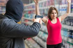 Robbery concept. Man in balaclava is aiming on woman in store. Stock Photos