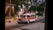 1961: parade led by official vehicle promenades down the neighborhood street Stock Footage