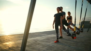 Sportive people training squats with trx near sea against sun. Slow motion. Stock Footage