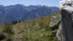 A man walking with his mountain bike on a trail in a European mountain range. Stock Footage