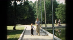 1961: man and boy walking down path HAGERSTOWN, MARYLAND Stock Footage