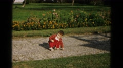 1961: young toddler boy sitting down on gravel sidewalk path HAGERSTOWN Stock Footage
