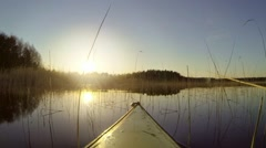 Kayaking in a summer evening through reeds towards the dazzling sun Stock Footage