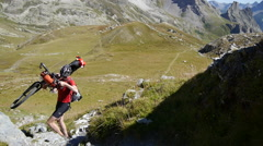 A man carrying his bike on a European mountain biking trail. Stock Footage