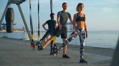 Sportive people training squats with trx near sea at sunrise. Slow motion. Stock Footage