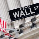 Wall street sign with the New York Stock Exchange on the backgro Stock Photos