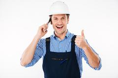 Builder in overall talking on phone and showing thumbs up Stock Photos
