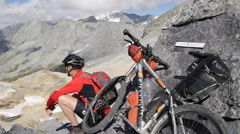 A mountain biker resting next to his bike in the mountains. Stock Footage