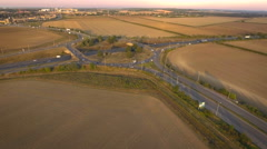 Busy road approaching highway junction roundabout, aerial view Stock Footage