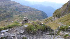 A scenic mountainside view with a cairn trail marker. Stock Footage
