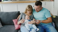 A young family with a baby at home. Naughty baby, dad stroking his belly. The Stock Footage
