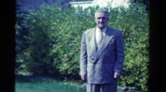 1958: an old man in formal suit standing on the lawn of the garden MINNESOTA Stock Footage