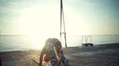 Back view of 3 persons work out with TRX near the sea slow motion Stock Footage