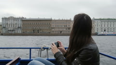 Girl sitting in a river bus on the go taking photos of architecture on a river Stock Footage