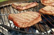 Grilled beef steaks cooking on barbecue grill Stock Photos