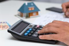 Hand on calculator - calculating household expenses Stock Photos
