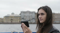Pretty girl takes photos in a city. She s glad, smiling, using her smartphone Stock Footage