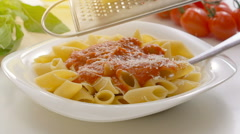 Male hands grating cheese over penne pasta with sauce Stock Footage