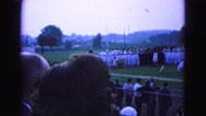 1964: gathering on the meadow to attend ceremony watched by many people Stock Footage